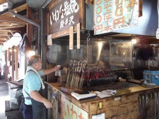 Fish grilling on their sticks at one of the food stands