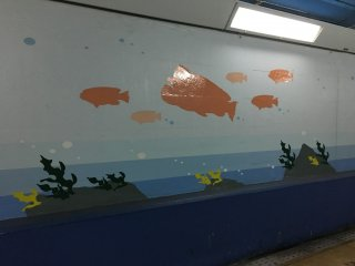 Lukisan ikan menutupi dinding terowongan.