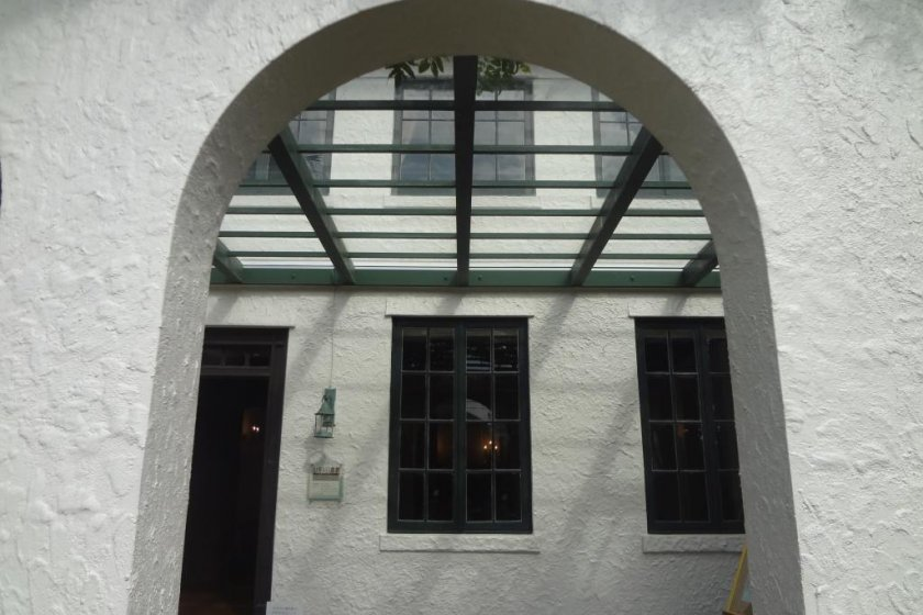 The façade of the house is typical Spanish colonial style: smooth plaster walls and semi-circular arcades