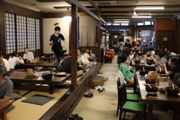 Traditional tatami-style booth and several wooden tables and chairs