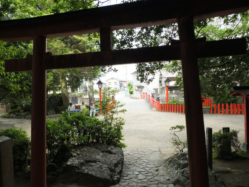 Locals hanging out on a bench in front of the shrine entrance