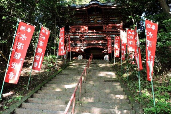 Degraus levando ao portão, ladeados de estandartes vermelhos