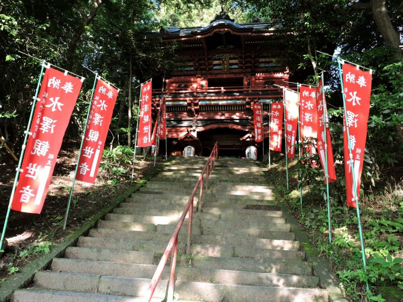 Steps up to the gate are flanked by red banners