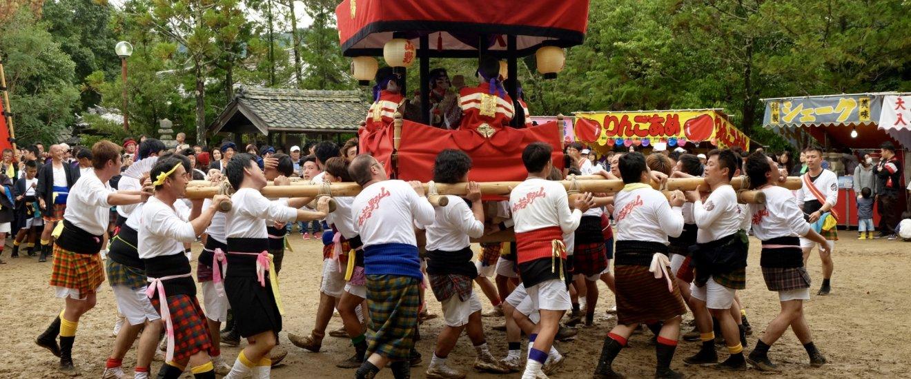 Cargando yotsudaiko (estructura de madera con 4 niños tocando los tambores)
