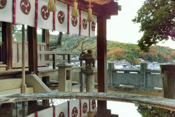 Urns full of water and autumn leaves reflect the shrine building