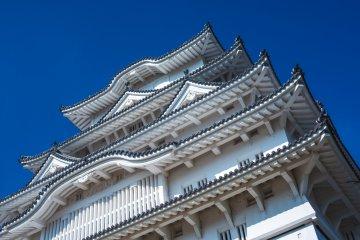 Looking up at blue skies behind Himeji Castle