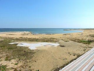 Um passeio pavimentado dá lugar a uma praia de areia