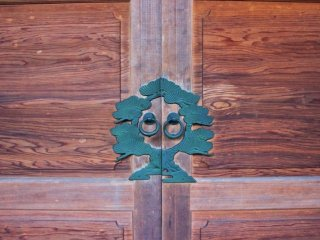Artisticly stunning door ornamention surrounding the ring pulls