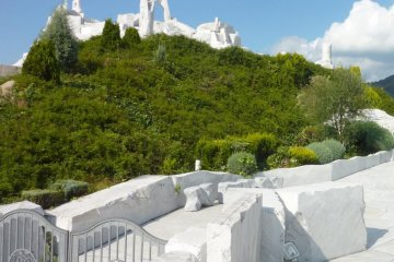 """Bright blue sky, lush greenery and brilliant white marble of """"The Heights of Eternal Hope for the Future"""" hill at Kosanji Temple"""