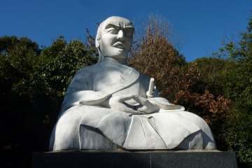 A large statue of Miyamoto Musashi looms over the parking lot