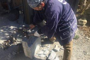 Craftsman showing how to make the stone lanterns