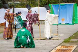 Preparing to begin the hassetsu, or 8 stages of shooting; the man in green is an attendant