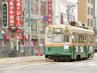 The green tram in front of the busy area of Hatchobori