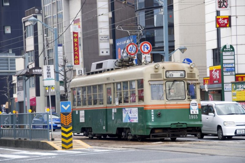 Tram stations are located in the center of busy street intersections.