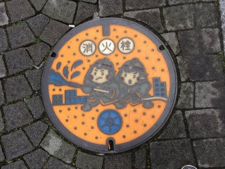 This manhole cover shows firefighters, indicating that a water hydrant is contained within
