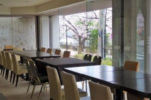 ห้องอาหารมีหน้าต่างกระจกจรดพื้นบานใหญ่ เปิดโอกาสให้ชมวิวแม่น้ำและดอกซากุระ