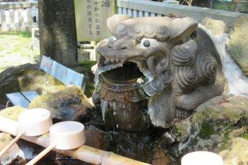 Мощная фигура у источника очищения напоминает о борцах сумо