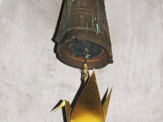 A bell inside the memorial with a crane
