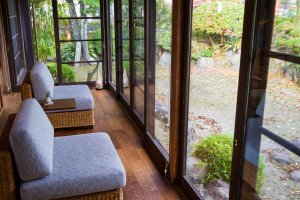 The engawa has lounge chairs facing a wall of windows bringing in the colors of the 300-year-old garden
