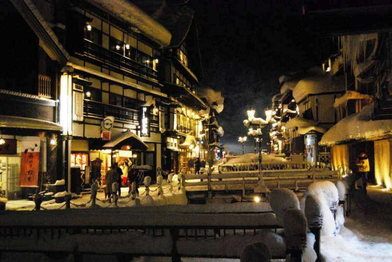 The yellow light from gas lanterns creates a romantic atmosphere at Ginzan Onsen