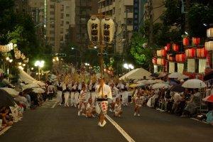 La foule se rassemble sur les côtés de la rue. Les danseurs ont ainsi plus de place, mais à moins d'arriver tôt, il est difficile d'avoir un bon point de vue