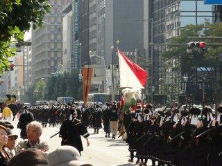 O público é muito numeroso, e enche os passeios ao lado das avenidas onde passa o desfile. Os figurantes do desfile também são muito numerosos, parece que toda a cidade de Quioto está nas ruas!