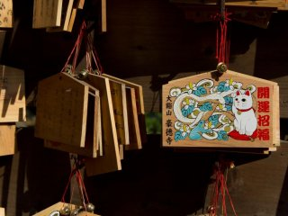 Wooden wishing plaques, called Ema, certainly feature the cat too