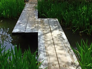A simple bridge of wooden planks allows visitors to cross this small stream.