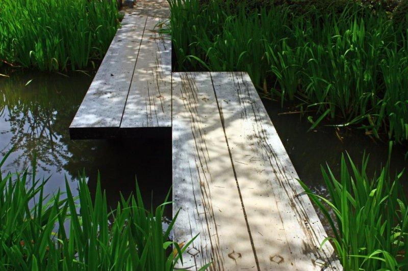 <p>방문객들이 작은 개울을 건널 수 있도록 지어진 단조로운 모양의 나무 판지 다리</p>