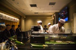 Koki yang menyiapkan sushi di belakang konter