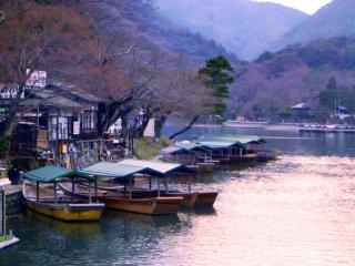 Ряды ряды ряду лодок мягко спускаются по течению в Арасияме