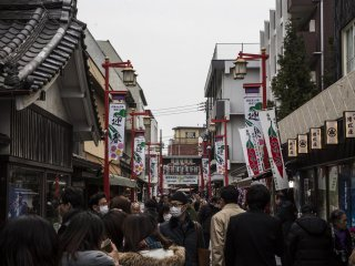 The street leading up to Sanmon, the main gate of Nishiarai Daishi Temple. It is filled with people milling around before the main Setsubun event.