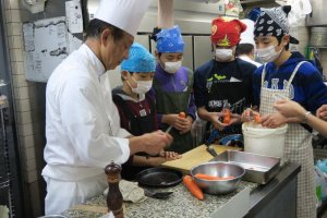 Students working with a Summit chef in the school kitchen