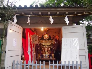 Mikoshi (palanquin) that is to be carried in the procession. On the left door is a sign posted informing visitors that there would be no procession this year. On the right is information on the shrine god (in Japanese).