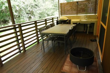 The covered back deck is ready for grilling and relaxing by the fire