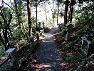 The entire path up to the cave is bordered with many stone lanterns and small statues