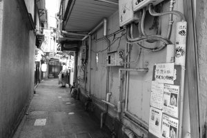 A tight alley squeezed between rampaging tall buildings where traditional Japanese and Chinese restaurants still exist
