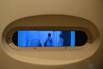 The camera inside this exhibit records the movements of passers by at high speed. This thin and wide blue LCD is able to replay the recorded movements several times over in many styles.