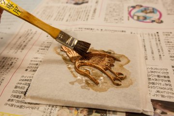 Applying glue to attach the gold leaf.