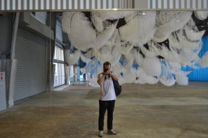 Oeuvre de Chiharu Shiota, composée de multitudes de bateaux en fils suspendus au plafond