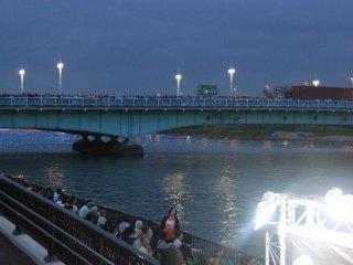 Đám đông cũng tụ tập ở trên cầu để theo dõi sự kiện. Ngay bên dưới, những chiếc đèn Led, hay còn được gọi là inori boshi (những ngôi sao cầu nguyện trong tiếng Nhật), bắt đầu lặng lờ trôi trên sông.