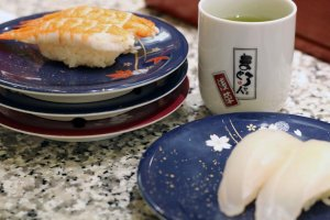 The pile of plates is growing. Here we see ebi (shrimp) and madai (red snapper). Enjoy complementary green tea with your meal.