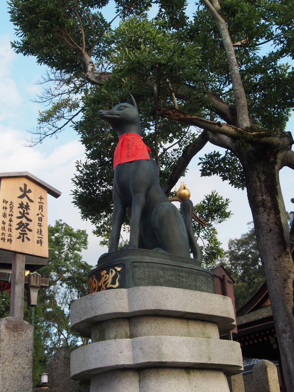 รูปปั้นคิซึตเนะด้านหน้าของอาคารศาลเจ้า