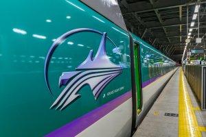 Photo of the Hokkaido Shinkansen with the logo on the side of the train