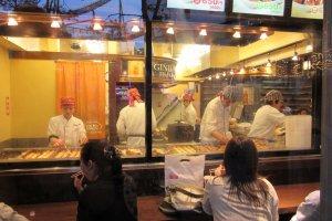 Chefs cooking takoyaki behind glass window