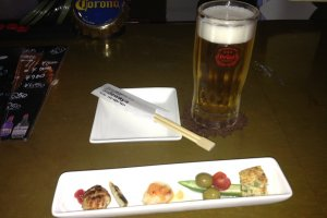 A plate of appetizers accompanies a first drink