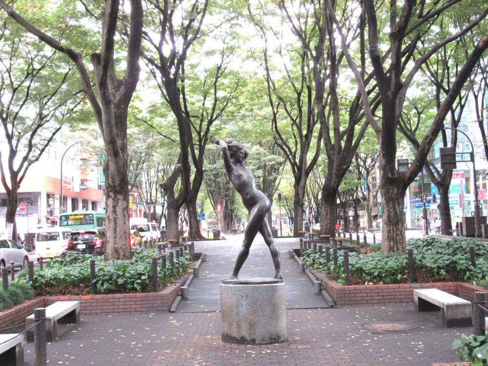 A modern sculpture and tall trees lining Jozenji Dori