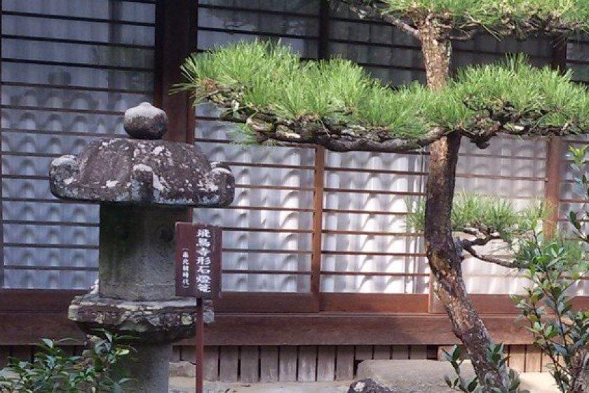 """""""飞鸟寺形石灯笼""""是飞鸟寺(别名""""安居院"""")的其中一件宝物。其背面刻有一个释迦牟尼悉昙梵文种子字和""""飞鸟寺""""字样。"""