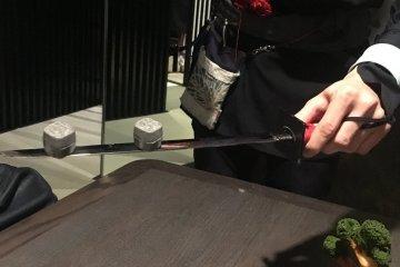 Сладкие крекеры, поданные на катане, японском мече.