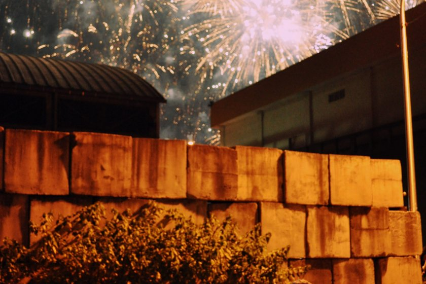 The fireworks are set off in the city bay, against the mountains.